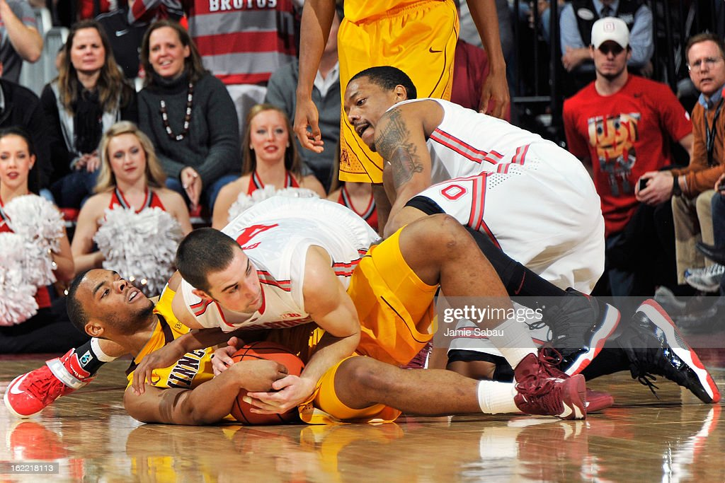 Julian Welch #0 of the Minnesota Golden Gophers and <a gi-track='captionPersonalityLinkClicked' href=/galleries/search?phrase=Aaron+Craft&family=editorial&specificpeople=7348782 ng-click='$event.stopPropagation()'>Aaron Craft</a> #4 of the Ohio State Buckeyes battle for a loose ball in the second half as Lenzelle Smith Jr. #32 of the Ohio State Buckeyes watches on February 20, 2013 at Value City Arena in Columbus, Ohio. Ohio State defeated Minnesota 71-45.