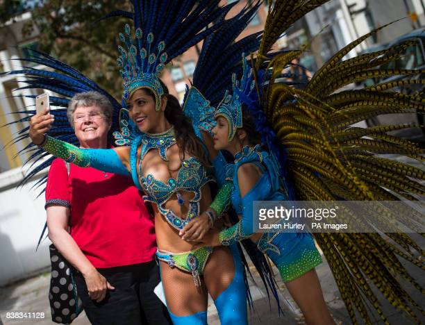 Juliana Campos and her nineyearold daughter Bella take a selfie with a passerby as they rehearse in full costume in the Notting Hill area of London...