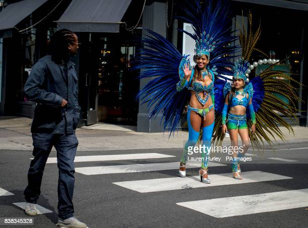 Juliana Campos and her nineyearold daughter Bella wave to a passerby as they rehearse in full costume in the Notting Hill area of London prior to...