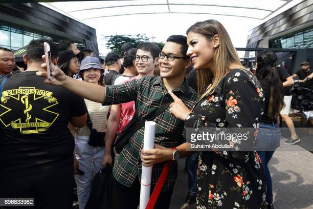 Julianna Penna poses for a selfie with a fan during the UFC Fan Experience at OCBC Square on June 17 2017 in Singapore