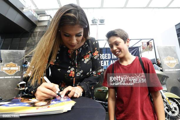 Julianna Penna signs autograph for a young fan at the Harley Davidson booth during the UFC Fan Experience at OCBC Square on June 17 2017 in Singapore