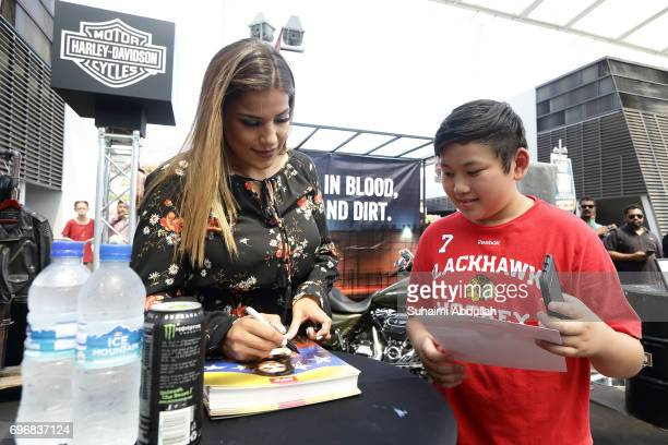 Julianna Penna signs autograph for fans at the Harley Davidson booth during the UFC Fan Experience at OCBC Square on June 17 2017 in Singapore