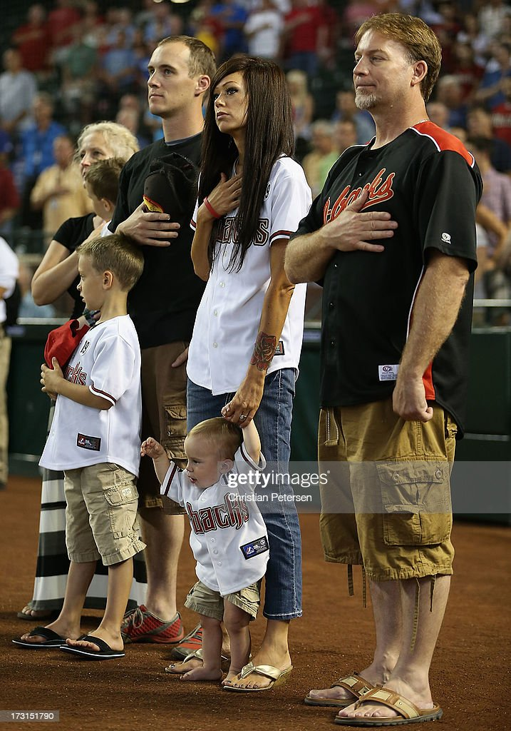 Julianne Ashcraft, wife to fallen firefighter Andrew Ashcraft, (c) stands attended for the National Anthem with family members before the MLB game between the Arizona Diamondbacks and the Los Angeles Dodgers at Chase Field on July 8, 2013 in Phoenix, Arizona. The Arizona Diamondbacks are honoring the 19 Granite Mountain Interagency Hotshot Crew firefighters who died battling a fast-moving wildfire near Yarnell, AZ.