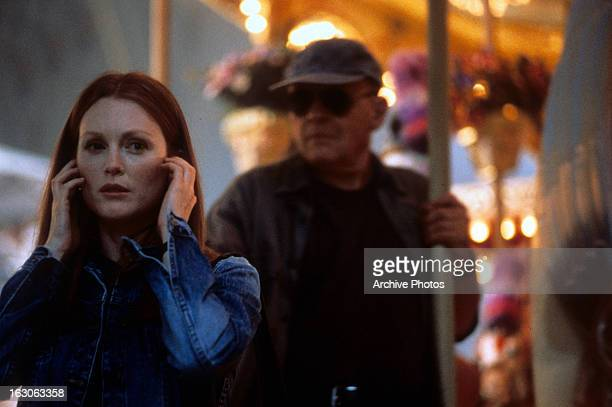 Julianne Moore holds a phone as she is being watched by Anthony Hopkins in a scene from the film 'Hannibal' 2001