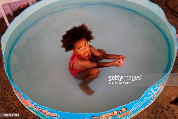 Julianys Alexandra Carrasquillo plays in a kiddie pool in the aftermath of Hurricane Maria in Loiza Puerto Rico September 28 2017 The US island...