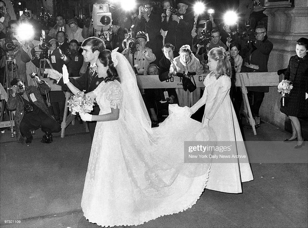 Julie and David Eisenhower leave Marble Collegiate Church after their wedding. Tricia Nixon, Bridesmaid, holds the train of Julie's wedding gown.