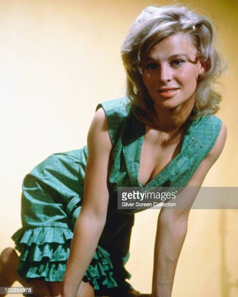 Julie Christie British actress wearing a green dress kneeling and leaning toward the camera in a studio portrait against a yellow background circa...