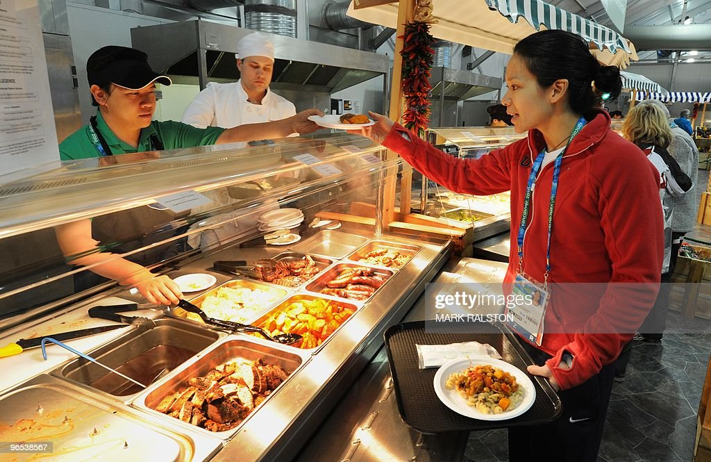 Julie Chu from the USA Women's Hockey team chooses food in the Winter Olympic athletes dining hall during a media tour of the Olympic Village in...
