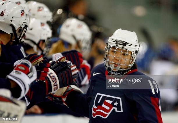 Julie Chu of the United States is congratulated by teammates after scoring in the first period to go up 10 over Finland during the women's ice hockey...