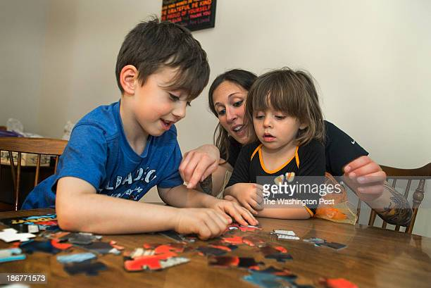Julie Gloster a single mother of three who was widowed last year does a puzzle with her son Colin and daughter Sophie at home in the Crossroads...