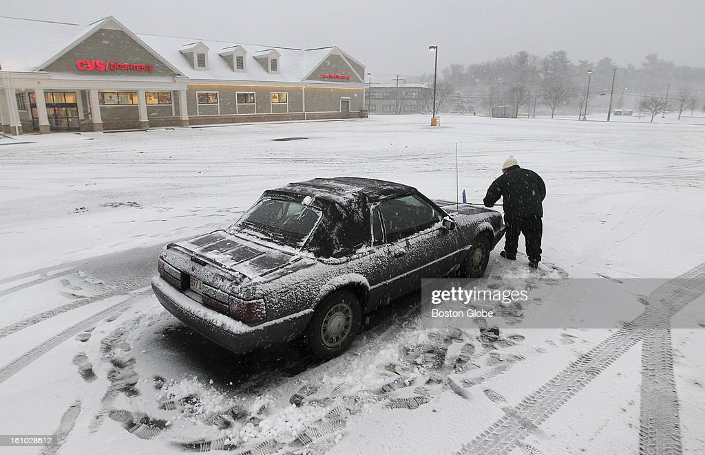 Julie Verrochi cleans her car off (the last one in parking lot) after leaving her job at Roche Bros. Supermarket, closed early due to the storm.