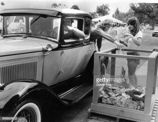 Julie Williams right helps volunteers from an antique car club pour cash donations into glass Container Channel 7 at Speer Boulevard and Lincoln...