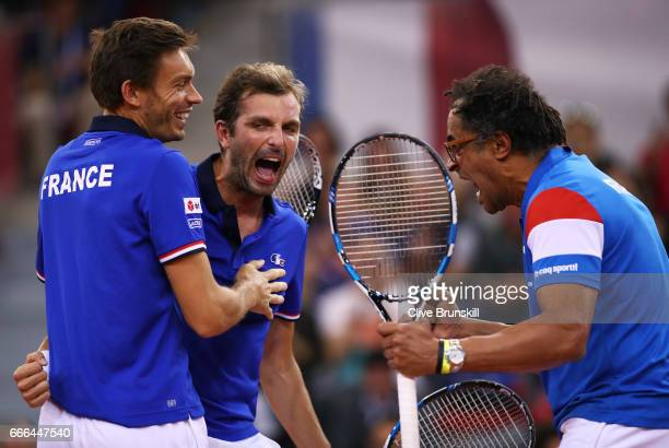 Julien Benneteau of France celebrates with Nicolas Mahut and captain Yannick Noah after all three went on court to play a point in the singles match...