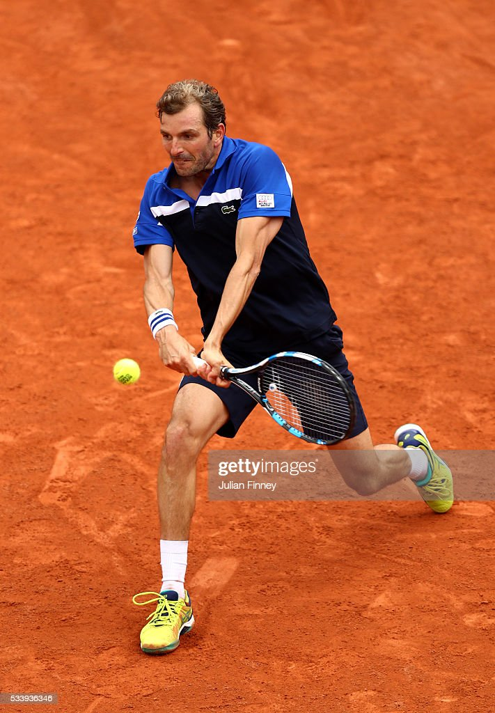 Julien Benneteau of France hits a backhand during the Men's Singles first round match against Lucas Pouille of France on day three of the 2016 French Open at Roland Garros on May 24, 2016 in Paris, France.