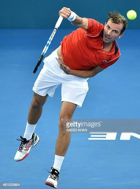 Julien Benneteau of France serves against Thanasi Kokkinakis of Australia in the men's singles match on day two of the Brisbane International tennis...