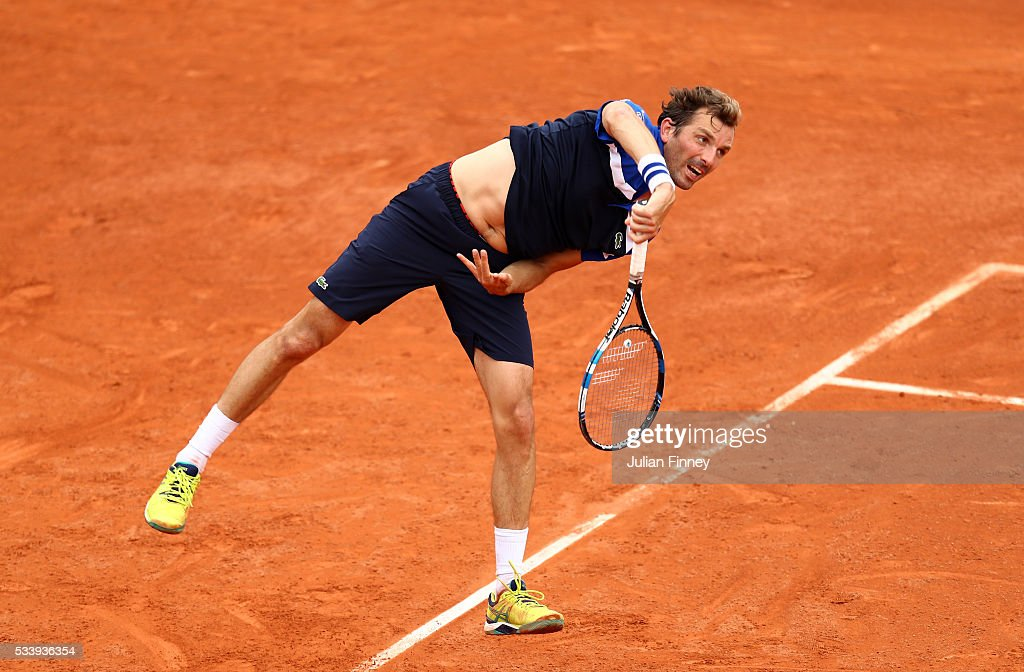 Julien Benneteau of France serves during the Men's Singles first round match against Lucas Pouille of France on day three of the 2016 French Open at Roland Garros on May 24, 2016 in Paris, France.