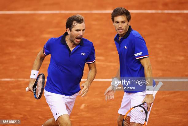 Julien Benneteau partnering Nicolas Mahut of France celebrate winning the third set in their doubles match against Jamie Murray and Dominic Inglot of...