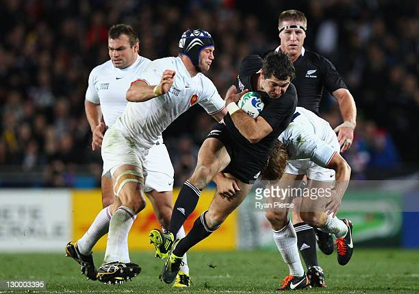 Julien Bonnaire and Aurelien Rougerie of France tackles Stephen Donald of the All Blacks during the 2011 IRB Rugby World Cup Final match between...