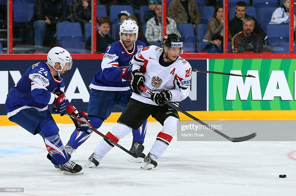Julien Desrosiers (L) of France and Thomas Vanek (R) of Austria battle for the puck during the IIHF World Championship group H match between France and Austria at Hartwall Areena on May 5, 2013 in Helsinki, Finland.