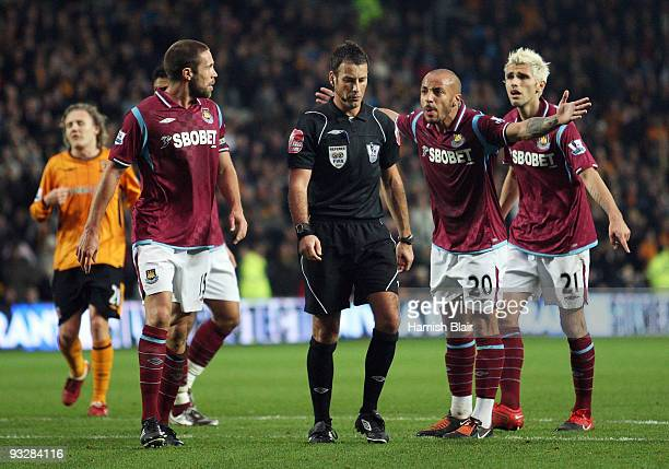 Julien Faubert of West Ham leads his team mates in protesting to referee Mark Clattenburg after Hull were awarded a penalty which led to their third...