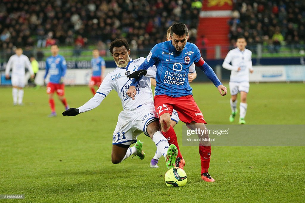 Julien Feret of Caen is tackled by Rincon of Troyes during the French Ligue 1 match between SM Caen and ESTAC Troyes at Stade Michel D'Ornano on...