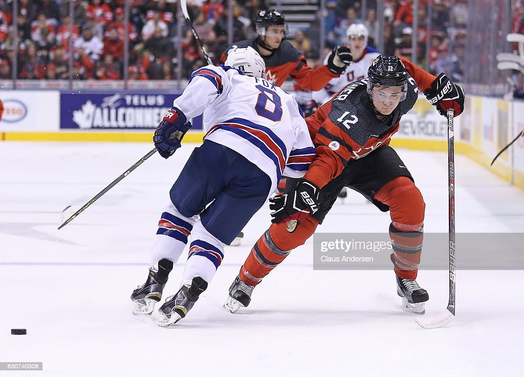 Julien Gauthier #12 of Team Canada side steps a hit by Adam Fox #8 of Team USA during a preliminary round game in the 2017 IIHF World Junior Hockey Championship at the Air Canada Centre on December 31, 2016 in Toronto, Ontario, Canada. The USA defeated Canada 3-1.