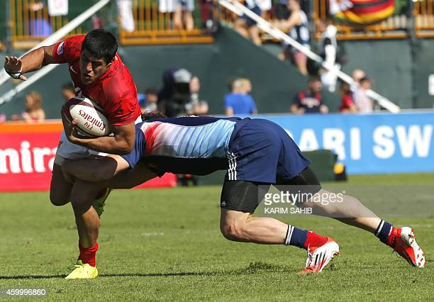 Julien Jane of France tackles Patricio Fernandez of Argentina during their rugby match on the first day of the Dubai leg of IRB's Sevens World Series...