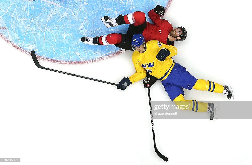 Julien Vauclair #3 of Switzerland falls to the ice with Jimmie Ericsson #42 in the first period during the Men's Ice Hockey Preliminary Round Group C game on day seven of the Sochi 2014 Winter Olympics at Bolshoy Ice Dome on February 14, 2014 in Sochi, Russia.