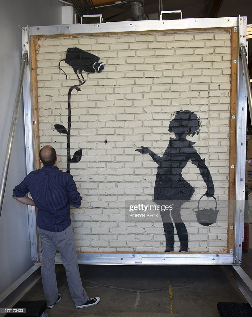 A Julien's Auctions employee examines a street art work by Banksy titled Flower Girl, at Julien's warehouse in Los Angeles, California August 21, 2013. 'Flower Girl,' a 9x8 foot (2.7 x 2.4 meter) mural on brick which was originally located at a Los Angeles gas station will headline Juliens Auctions Street Art auction in December. The owner of the gas station, before selling the property, decided to have the 9x8 foot section of the wall cut out and removed to bring it to auction. Banksy has not publicly commented on the impending sale of his art work. AFP PHOTO / Robyn Beck