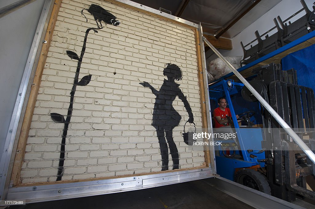 Julien's Auctions employee Nat Hebron drives a forklift past a work by Banksy titled Flower Girl, at Julien's warehouse in Los Angeles, California August 21, 2013. 'Flower Girl,' a 9x8 foot (2.7 x 2.4 meter) mural on brick which was originally located at a Los Angeles gas station, will headline Juliens Auctions Street Art auction in December. The owner of the gas station, before selling the property, decided to have the 9x8 foot section of the wall cut out and removed to bring it to auction. Banksy has not publicly commented on the impending sale of his art work. AFP PHOTO / Robyn Beck