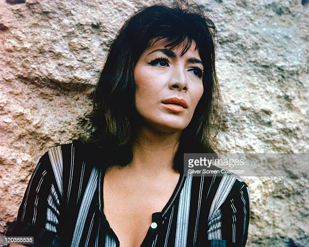 Juliette Greco French actress and singer wearing a black blouse with vertical white stripes posing against a rock circa 1965