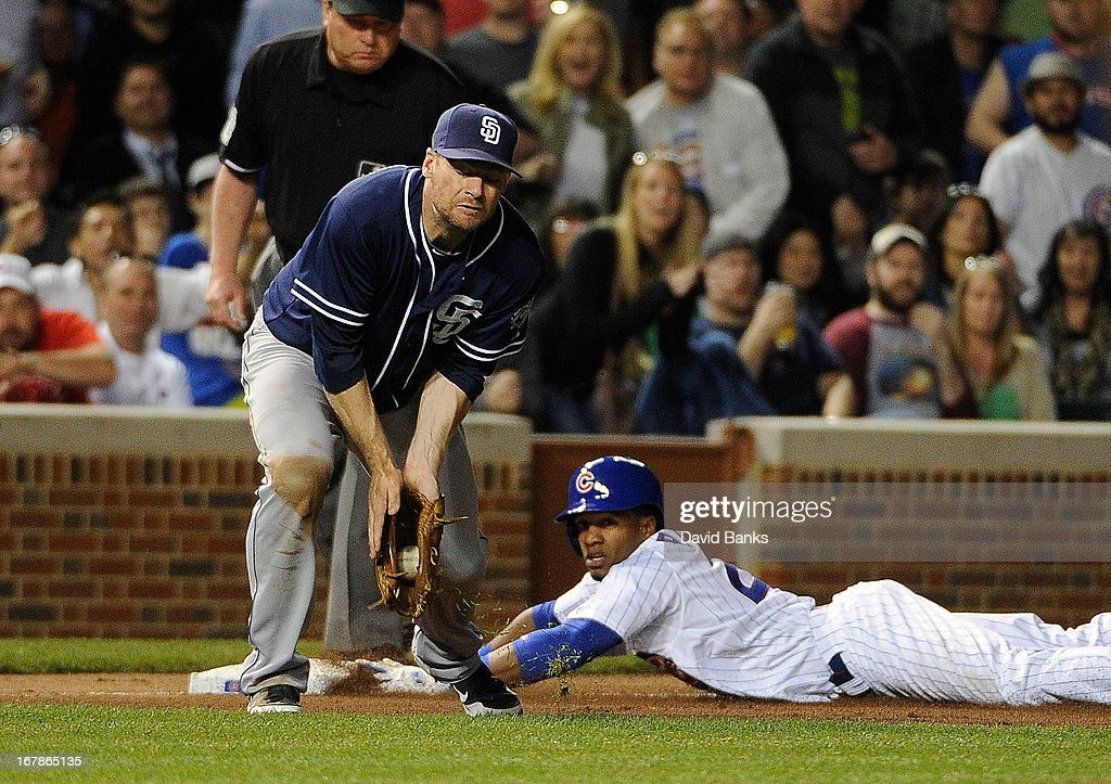 Julio Borbon #20 of the Chicago Cubs is safe at third base as Chase Headley #7 of the San Diego Padres takes the throw during the fourth inning on May 1, 2013 at Wrigley Field in Chicago, Illinois.