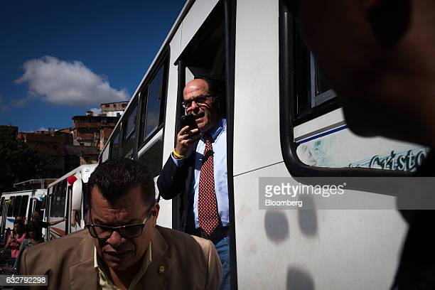Julio Borges president of the National Assembly center exits a bus while speaking on his smartphone before a session of the National Assembly at the...