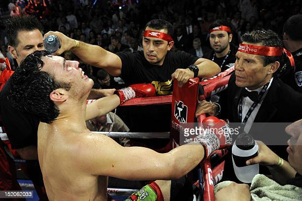 Julio Cesar Chavez Jr and Julio Cesar Chavez Sr await the decision in their corner after the fight against Sergio Martinez for their WBC middleweight...
