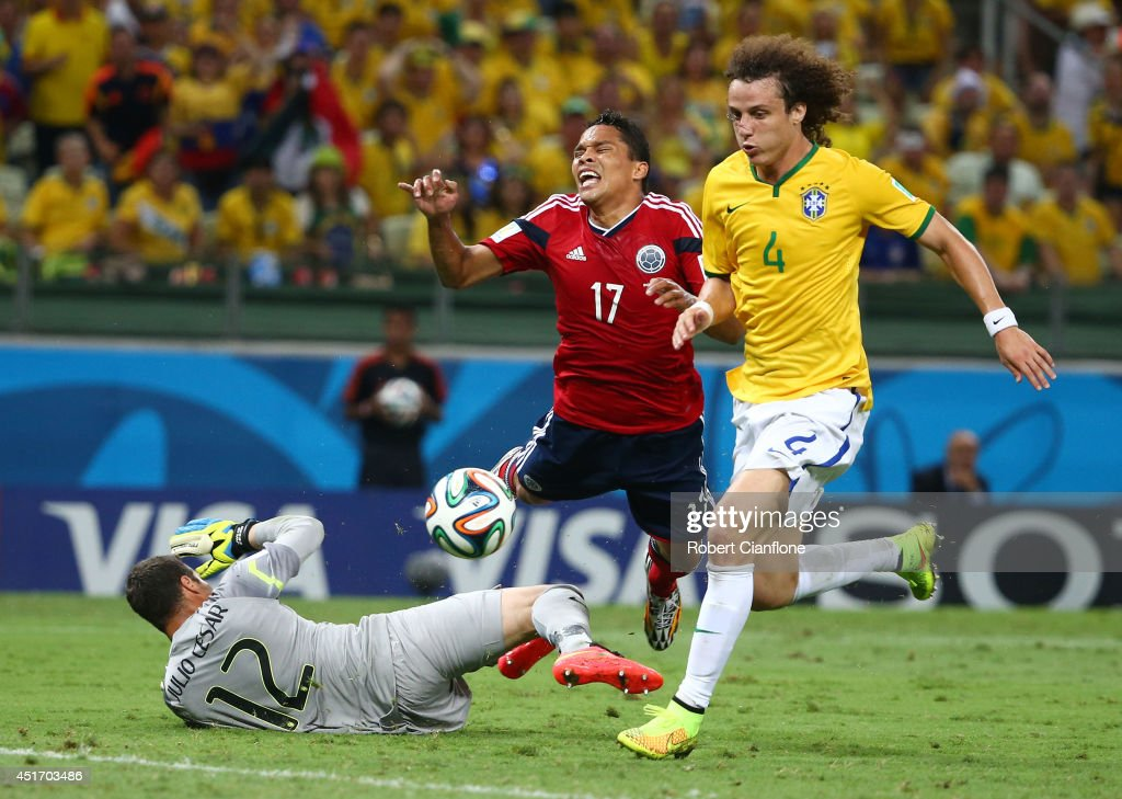 Julio Cesar of Brazil challenges Carlos Bacca of Colombia resulting in a penalty kick and yellow card for Cesar as David Luiz defends during the 2014...