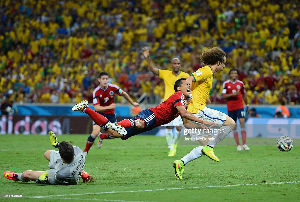 Julio Cesar of Brazil challenges Carlos Bacca of Colombia resulting in a penalty kick and yellow card for Cesar as David Luiz defends during the 2014 FIFA World Cup Brazil Quarter Final match between Brazil and Colombia at Castelao on July 4, 2014 in Fortaleza, Brazil.