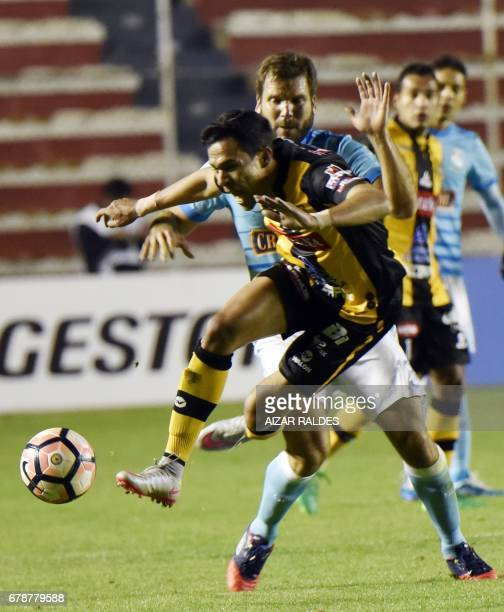 Julio Cesar Perez of Bolivia's The Strongest vies for the ball with Renzo Revoredo Zuazo of Peru's Sporting Cristal during their Copa Libertadores...