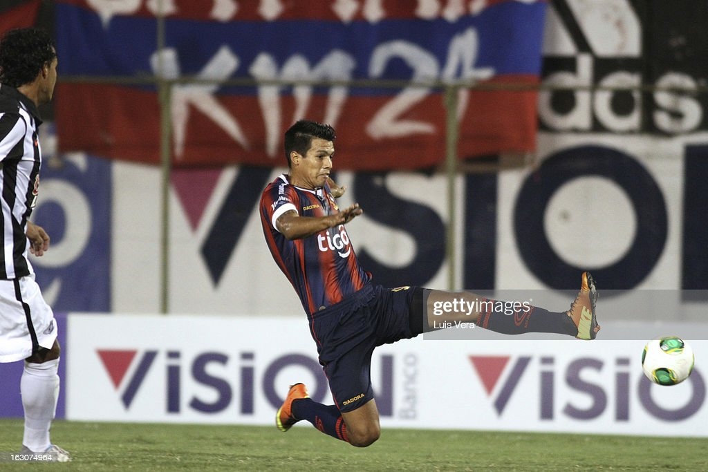 Julio Dos Santos (R) of Cerro Porteño and Sergio Aquino (L) of Libertad fight for the ball during the match between Libertad and Cerro Porteño for the Aperture APF, at Defensores del Chaco on March 03, 2013 in Asuncion, Paraguay.