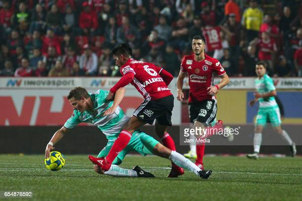 Julio Furch of Santos Juan Valenzuela of Tijuana and Guido Rodriguez of Tijuana fight for the ball during the 11th round match between Tijuana and...