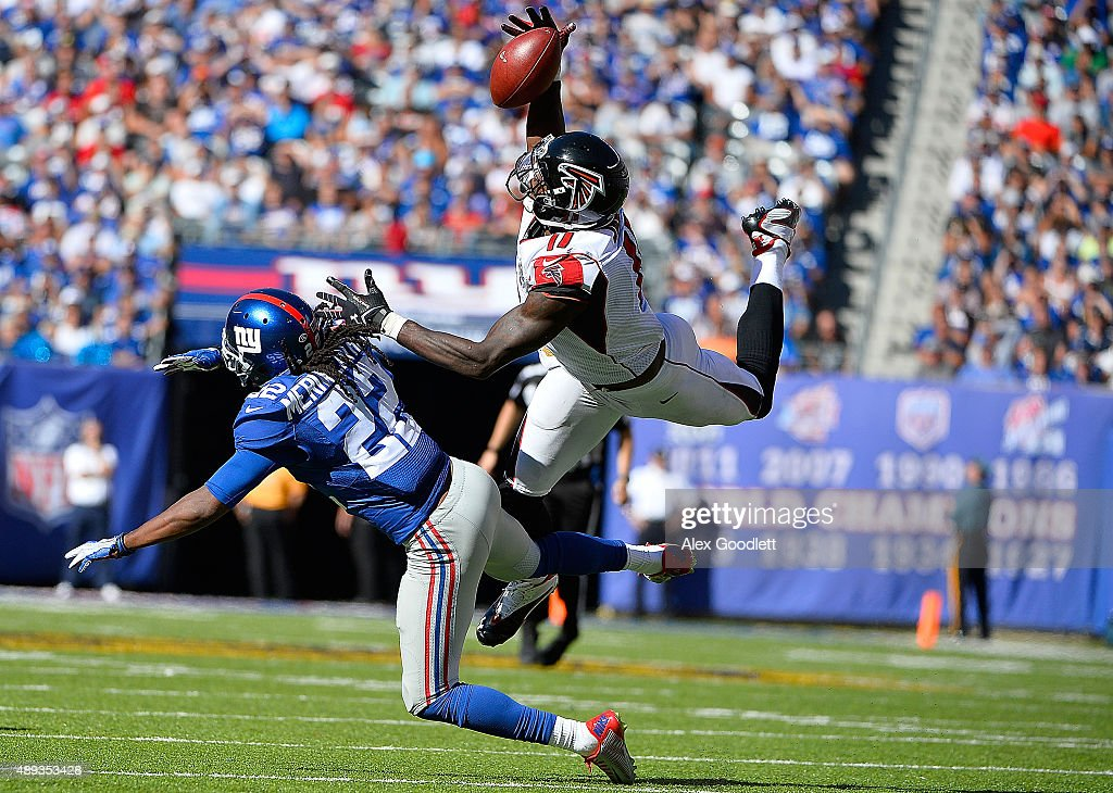 Julio Jones of the Atlanta Falcons makes a first down reception in the fourth quarter under pressure from Brandon Meriweather of the New York Giants...