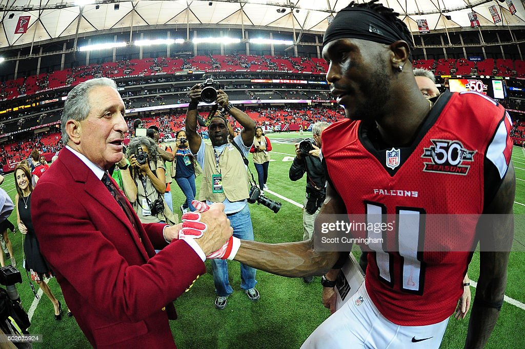 Julio Jones of the Atlanta Falcons shakes hands with team owner Arthur Blank after beating the Carolina Panthers at the Georgia Dome on December 27...
