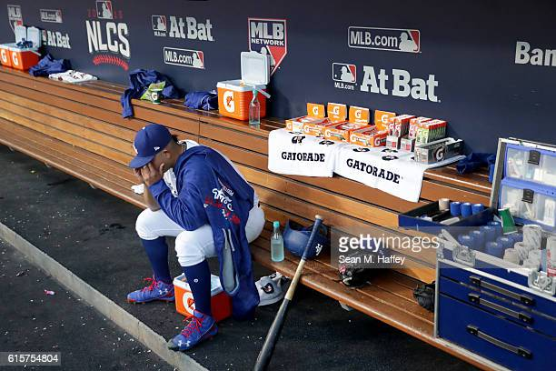 Julio Urias of the Los Angeles Dodgers sits in the dugout after being taken out of the game in the fourth inning against the Chicago Cubs in game...