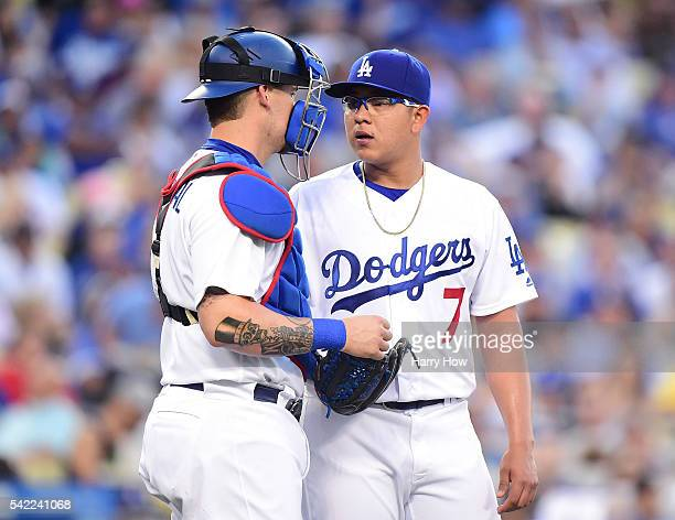 Julio Urias of the Los Angeles Dodgers speaks with Yasmani Grandal during the second inning against the Washington Nationals at Dodger Stadium on...
