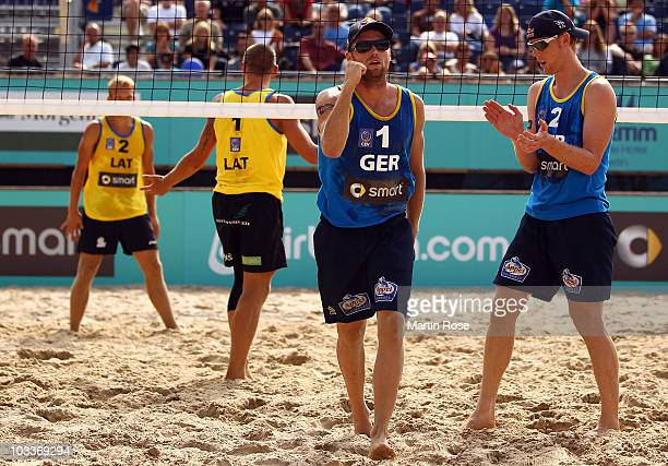 Julius Brink of Germany celebrates with team mate Jonas Reckermann during the match between Martins Plavins and Janis Smedins of Latvia and Julius...