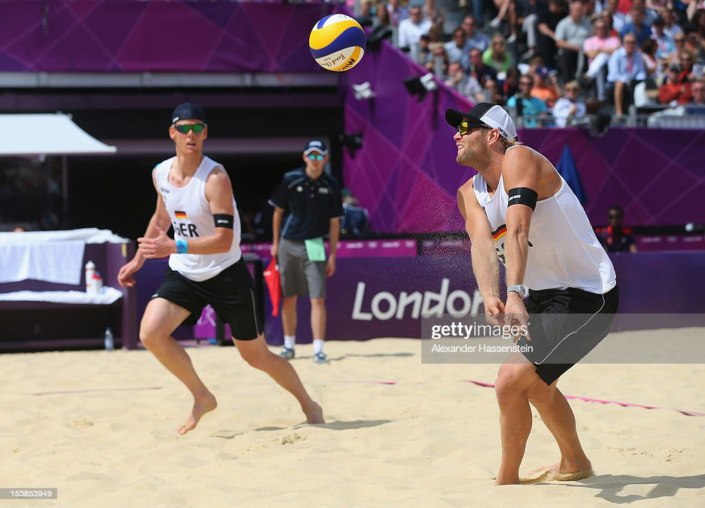 <a gi-track='captionPersonalityLinkClicked' href=/galleries/search?phrase=Julius+Brink&family=editorial&specificpeople=224931 ng-click='$event.stopPropagation()'>Julius Brink</a> (R) of Germany plays the ball with his team mate <a gi-track='captionPersonalityLinkClicked' href=/galleries/search?phrase=Jonas+Reckermann&family=editorial&specificpeople=228457 ng-click='$event.stopPropagation()'>Jonas Reckermann</a> during the Men's Beach Volleyball match between Germany and Russia on Day 1 of the London 2012 Olympic Games at the Horse Guards Parade on July 28, 2012 in London, England.