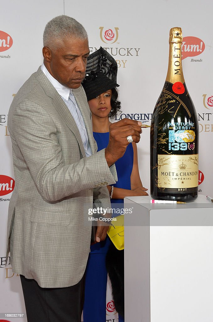 "Julius ""Dr. J"" Erving signs the Moet & Chandon 6L for the Churchill Downs Foundation during the Kentucky Derby at Churchill Downs on May 4, 2013 in Louisville, Kentucky."
