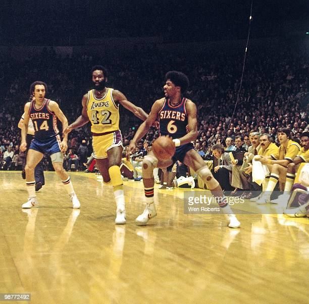 Julius Erving of the Philadelphia 76ers drives the ball up court against Connie Hawkins of the Los Angeles Lakers during a game played circa 1980 at...