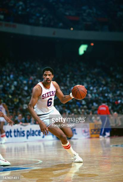 Julius Erving of the Philadelphia 76ers drives with the ball against the New Jersey Nets during an NBA basketball game circa 1983 at The Spectrum in...