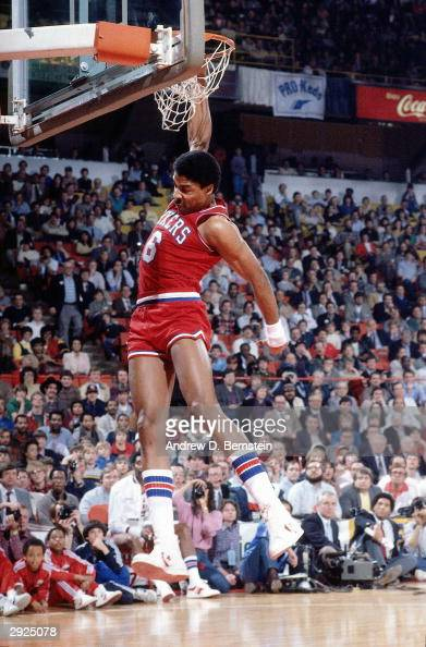 Julius Erving of the Philadelphia 76ers follows through on his dunk during the Slam Dunk contest during AllStar Weekend circa 1984 at McNichols Arena...