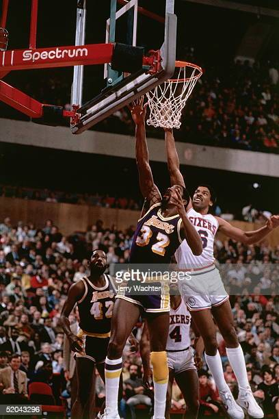 Julius Erving of the Philadelphia 76ers goes up to block a shot against Magic Johnson of the Los Angeles Lakers during an NBA game circa 1983 at the...
